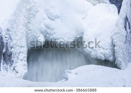 Icicles and snow near flowing water - stock photo