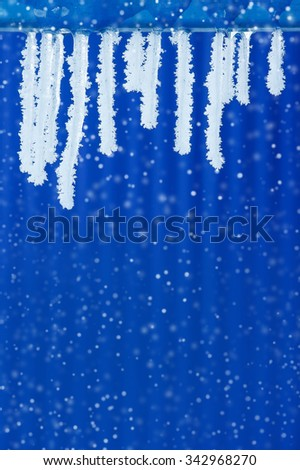 Icicles covered with hoarfrost on a blue background - stock photo
