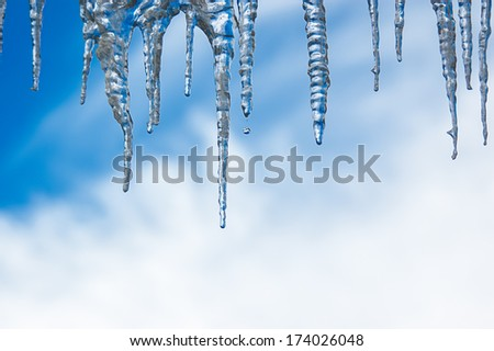Icicles dripping in a winter storm against a cloudy sky - stock photo