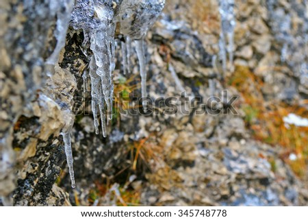 Icicles, freezing of dripping water, hanging on stone wall during winter - stock photo
