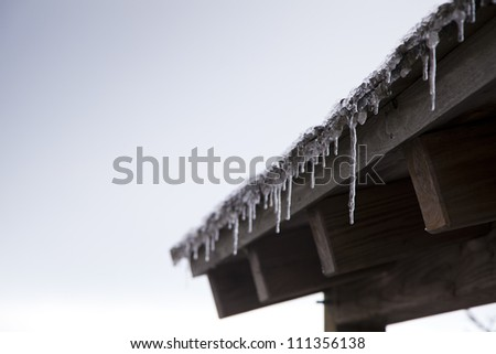 Icicles hang from the roof of a cabin.