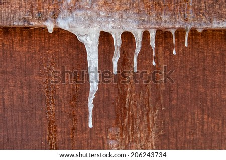 icicles hanging down on a wooden wall - stock photo