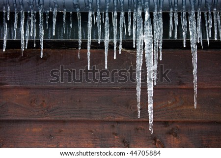 Icicles hanging from a drainpipe on the exterior of a wooden panelled house.