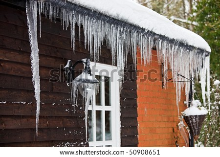 Icicles hanging from a lamp on the exterior of a panelled wooden house with a white windowed door. Photo has relatively short depth of field, with focus on the lamp covered with icicles. - stock photo