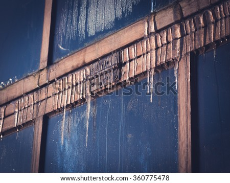 Icicles have formed during the cold night on an old window with a wooden frame at the Botanical Gardens in Lund, Sweden. The ice on the window glass is melting in the morning sun. Vintage faded look.  - stock photo