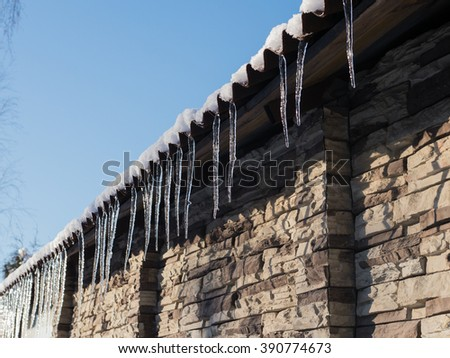 icicles on a roof at sunny winter day