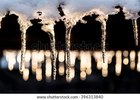 Icicles on black background and shiny lights. Icicles in sunset. - stock photo