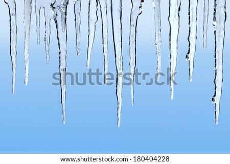 Icicles on blue background - stock photo