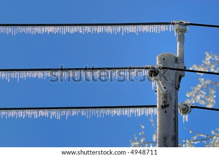 Icicles on row of powerlines after ice storm, against blue sky - stock photo