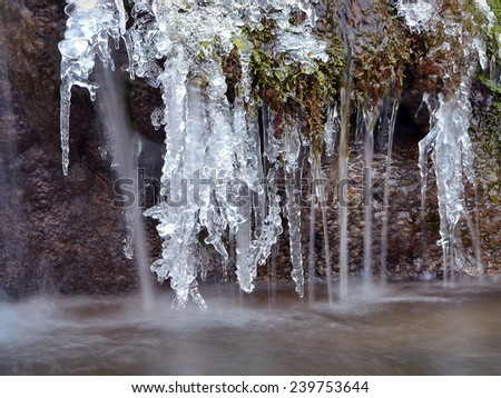 Icicles on stream cascades - stock photo