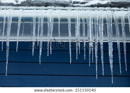 Icicles on the roof. Winter concept. Blue wooden background.  - stock photo