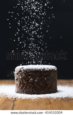 Icing sugar falling on Chocolate Lava Cake. Chocolate pudding sitting on a rustic wooden table.