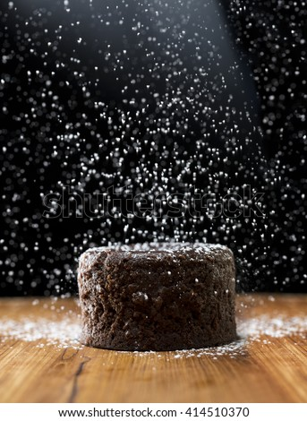 Icing sugar falling on Chocolate Lava Cake. Chocolate pudding sitting on a rustic wooden table. - stock photo