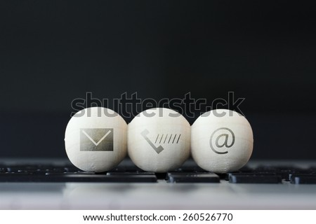 icon on wooden ball of website and internet contact us page concept on computer laptop  keyboard - stock photo