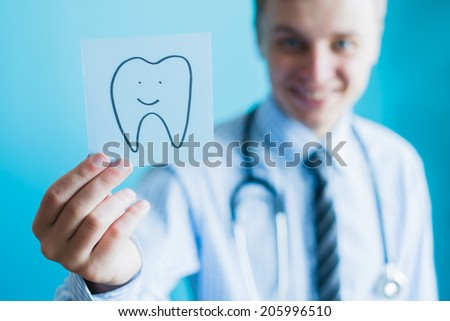 icon tooth in his hand - stock photo