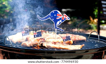 Iconic Australian BBQ close up of man cooking chops, sausages and steak, outdoors in garden setting.