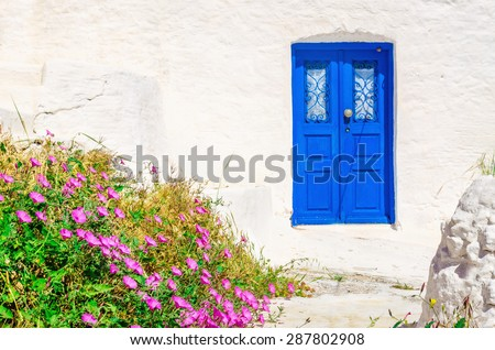 Iconic blue wooden door against clear white wall and colorful flowers. Typical view for Greek islands, Greece - stock photo