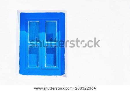 Iconic blue wooden window against clear white wall. Typical view for Greek islands, Greece - stock photo