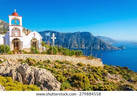 Iconic church with red roof on cliff over sea bay on Greek island, Greece - stock photo