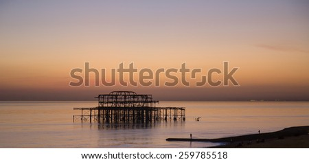 Iconic landmark Brighton West Pier at Sunset, with calm sea and the lights of Bognor Regis in distance. - stock photo