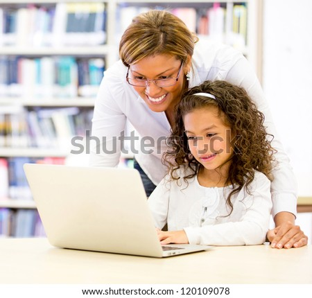ICT teacher with a young student using the computer - stock photo