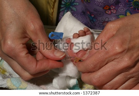 ICU nurse tending to the IV of an infant - stock photo
