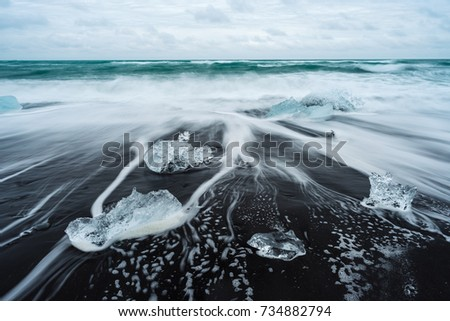 Icy beach in Iceland, Europe. Ice on the black volcanic sand on the Atlantic Ocean. Tourist attraction. Amazing landscape cloudy day. World beauty.