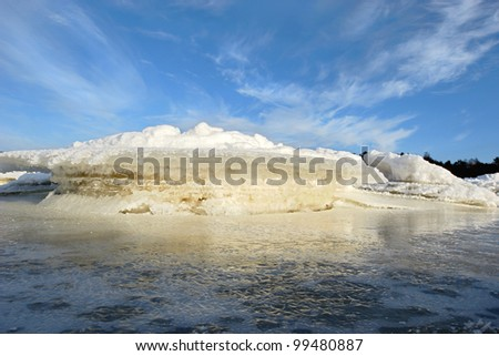 icy coastline with bright blue sky in sunny morning