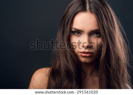 Icy glance. Serious young woman looking at camera while standing against black background   - stock photo