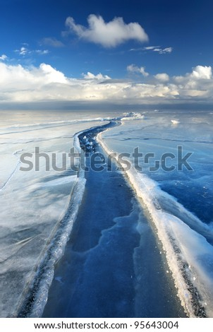 Icy road and bright sky. Winter composition - stock photo