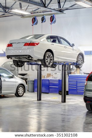 Idaho Falls, Idaho, USA Oct. 8, 2015 Cars being worked on in a a modern repair shop. - stock photo
