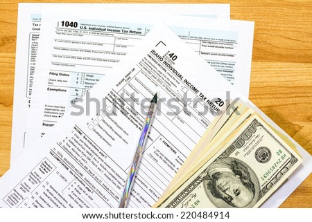 Idaho individual tax forms and one hundred dollar bills - stock photo
