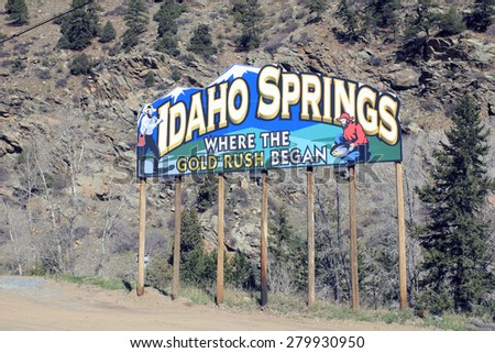 Idaho Springs, CO, USA - April 23, 2014: Large and colorful entry sign side Interstate 70 near town saying Idaho Springs Where the Gold Rush Began. man stands with mining pick  man pans for gold  - stock photo