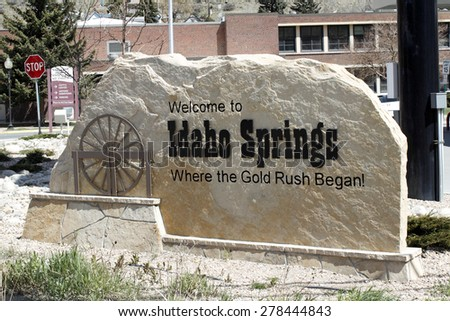 Idaho Springs, CO, USA - April 23, 2014: Large tan stone that has written on and carved into it, Welcome to Idaho Springs, Where the Gold Rush Began! The sign has a brown sculpture of a water wheel