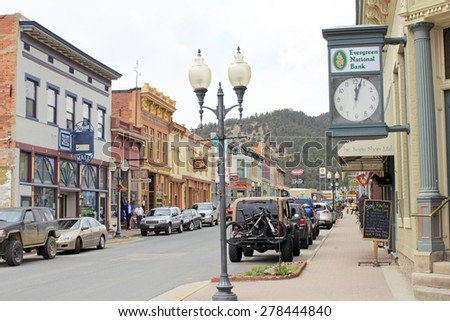 Idaho Springs, CO, USA - April 21, 2014: People shop in historical buildings stores, restaurants and more enjoying the spring day on Miner Street in downtown. Many old and colorful buildings  - stock photo