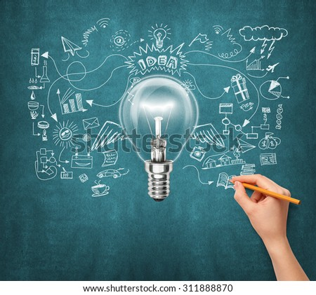 Idea background with lamp, sketch and human hand with pencil - stock photo