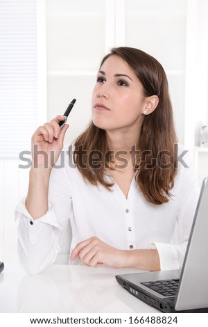 Idea: business woman thinking with pen in hand at Office. - stock photo