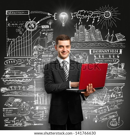 Idea concept. Business man in suit with laptop in his hands, looking on camera, with lamp above his head - stock photo