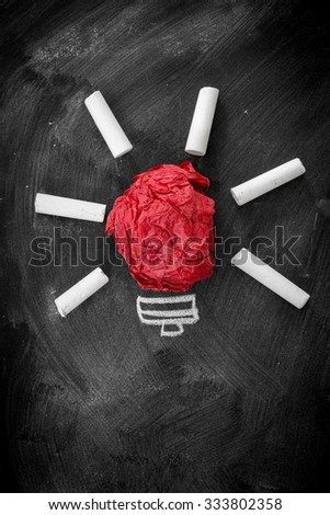 Idea concept, crumpled red paper on the chalkboard turned into a light bulb - stock photo