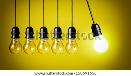 Idea concept on yellow background. Perpetual motion with light bulbs - stock photo