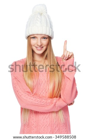 Idea concept. Portrait of woman on white background wearing woolen hat and sweater directing finger up, over white background