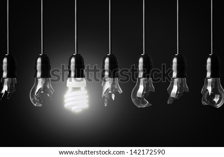 idea concept with broken bulbs and one glowing energy saving bulbs