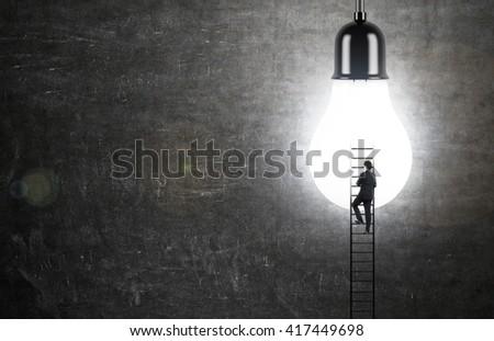 Idea concept with businessman climbing ladder to illuminated lightbulb on chalkboard background - stock photo
