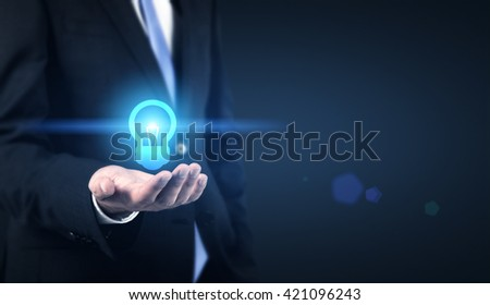 Idea concept with businessman holding abstract illuminated lightbulb icon on dark background