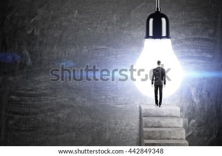 Idea concept with businessman standing on concrete ladder against huge illuminated light bulb on chalkboard background - stock photo