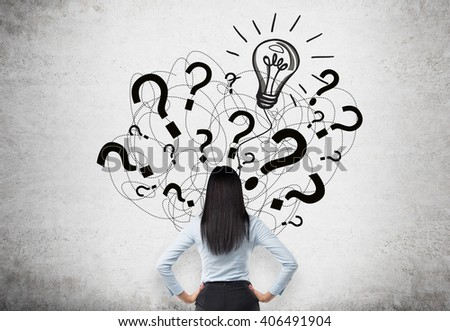 Idea concept with businesswoman facing question mark and bulb sketch on concrete wall - stock photo