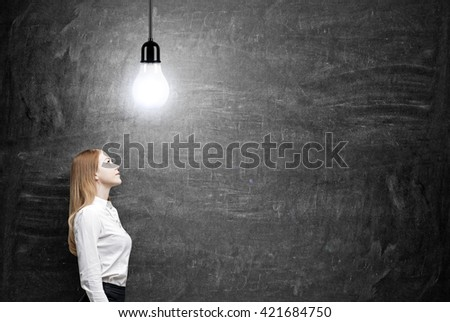 Idea concept with businesswoman looking up at ceiling lamp on chalkboard background - stock photo