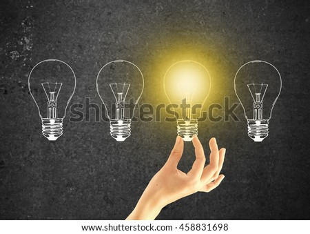 Idea concept with female hand holding abstract illuminated light bulb on dark concrete background - stock photo