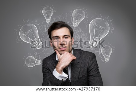 Idea concept with light bulb drawings around handsome businessman portrait