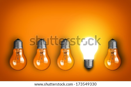 Idea concept with row of light bulbs and glowing bulb - stock photo
